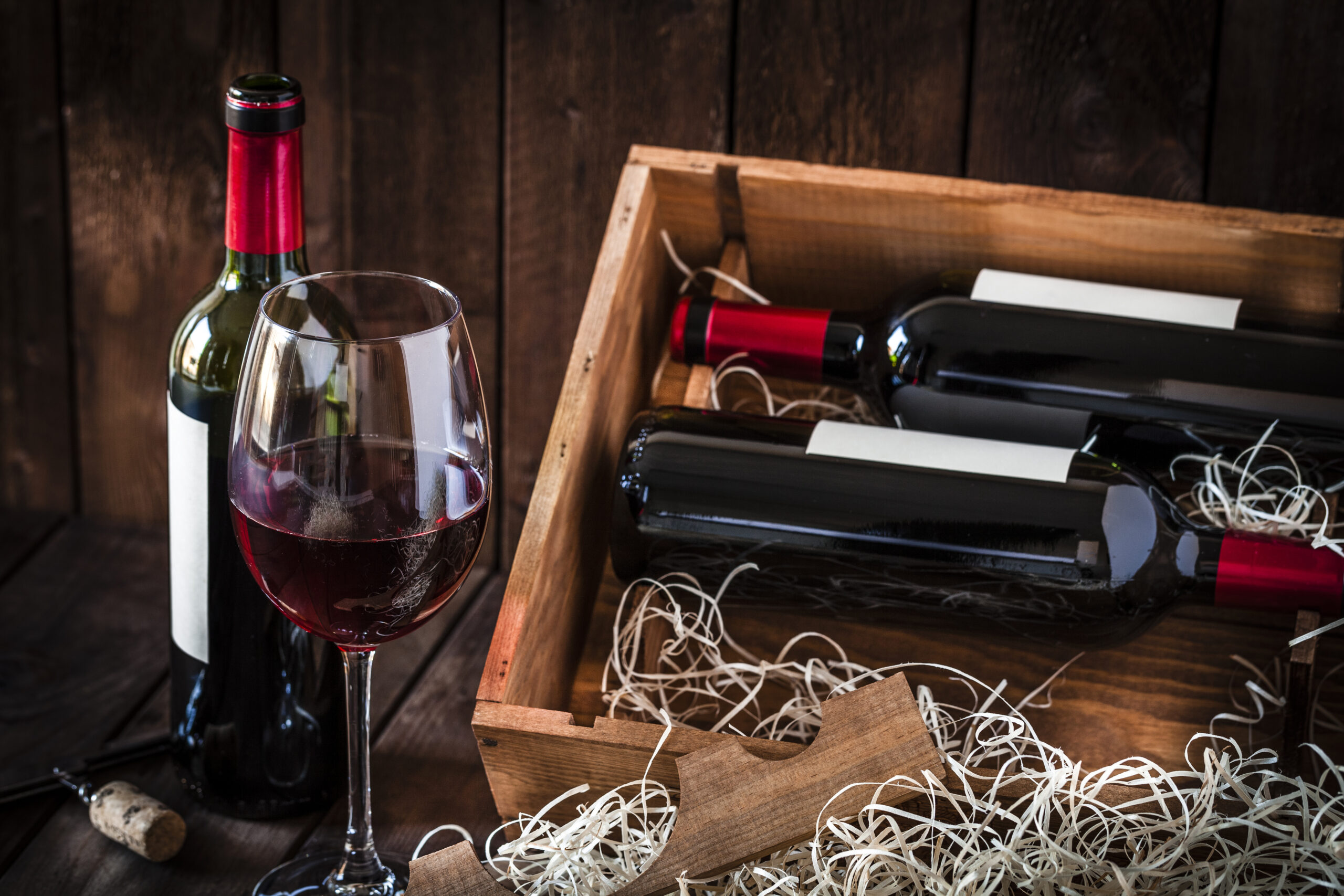 Front view of a wooden box with two wine bottles inside it and a third bottle out the box with a wineglass in front of it. A corkscrew with a cork is in besid the wineglass. Predominant color is brown. Low key DSRL studio photo taken with Canon EOS 5D Mk II and Canon EF 100mm f/2.8L Macro IS USM